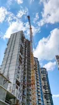 Image of high building crane on construction site of new modern district against blue sky with white clouds