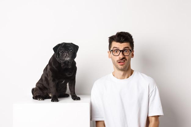 Immagine del proprietario di un cane hipster seduto vicino a un simpatico carlino nero, che fissa la telecamera confusa e perplessa, sfondo bianco.