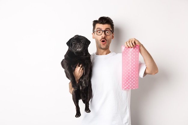 Image of hipster guy pet owner, holding cute black pug and dog poop bag, standing over white background.