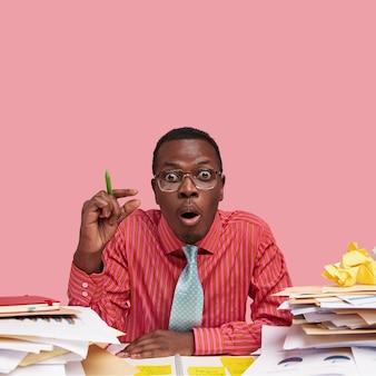 L'immagine di un esperto finanziario inorridito mostra l'ammontare delle sue entrate, stordito dai costi futuri, analizza la documentazione, indossa una camicia formale rosa