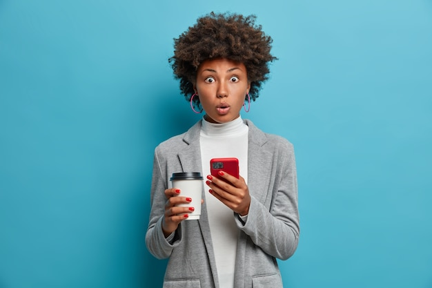 Image of impressed african american business lady holds paper cup and smartphone