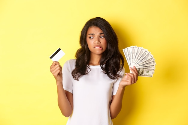 Image of indecisive africanamerican girl making choice between money and credit card standing