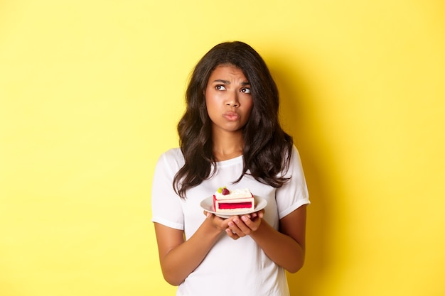 Image of indecisive and sad african-american woman, looking upset, cannot eat cake, standing over yellow background
