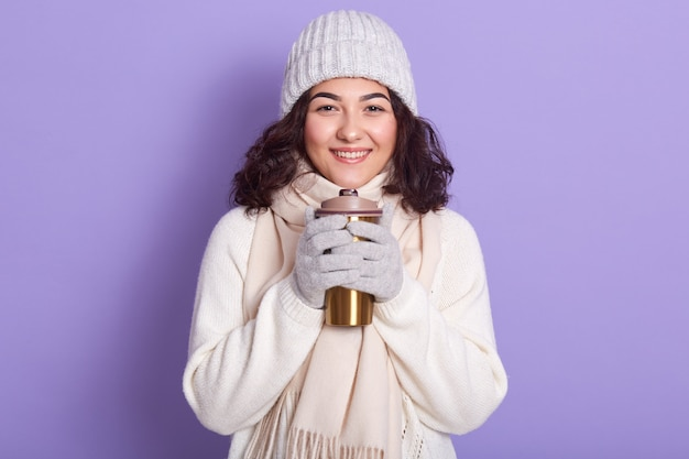 Image of inspired smiling pretty model with dark curly hair holding thermal mug, being in good mood, spending time alone in studio