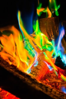 Image of iridescent tongues of fire lick at ashen logs