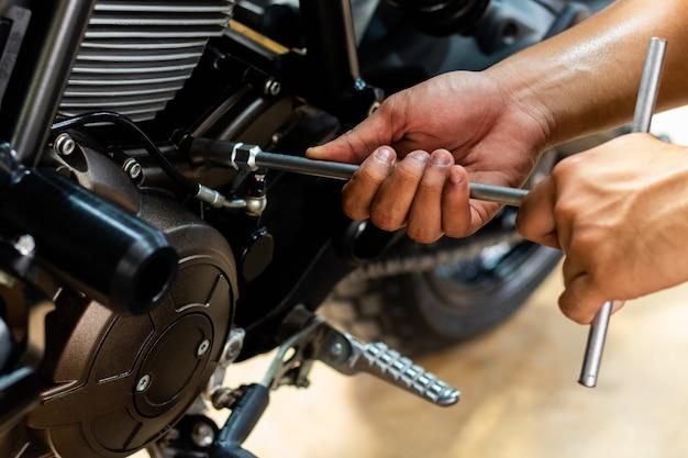 Image is close up, 사람들은 오토바이를 수리하고 있습니다. 렌치와 드라이버를 사용하여 작업하십시오.