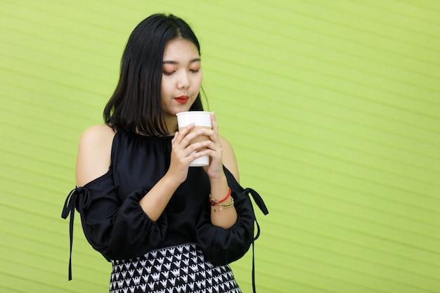 Изображение портретное. азиатская улыбающаяся полная женщина в черном платье. деловая женщина азии стоя, держа руку чашку кофе в зеленом фоне. концепция женского питья в студии.