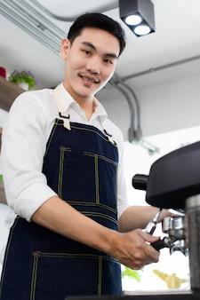 이미지는 초상화입니다. 아시아 젊은이는 커피 머신을 사용하여 미소를 짓습니다. 따뜻한 물로 커피를 헹굽니다. 카페에서 에스프레소나 아메리카노를 끓이기 위해 분쇄 커피를 준비하는 아시아 남자.