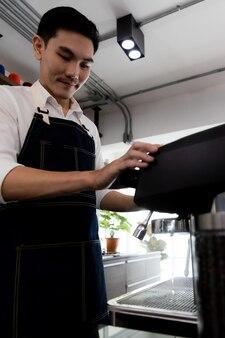 이미지는 초상화입니다. 커피 머신을 사용하는 아시아 청년은 미지근한 물로 커피를 헹굽니다. 카페에서 에스프레소나 아메리카노를 끓이기 위해 갈은 커피를 누를 준비를 하는 남자.