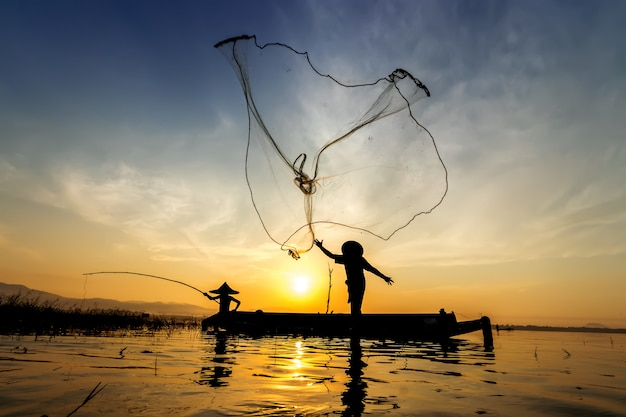 이미지는 실루엣입니다. 어부의 캐스팅은 우와 함께 아침 일찍 물고기에 나갑니다