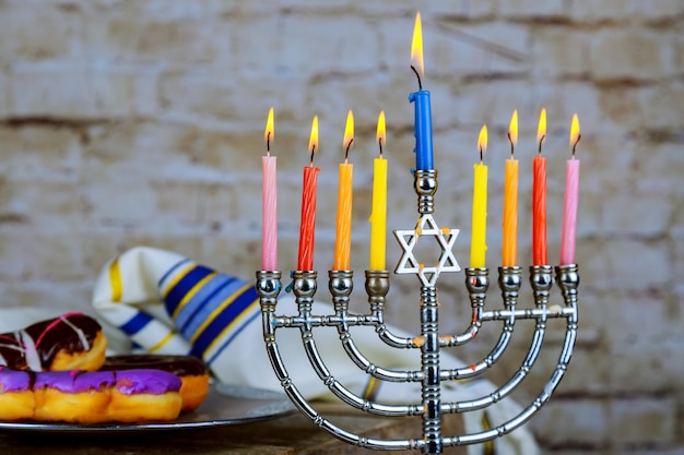 Image of jewish holiday hanukkah with menorah traditional candelabra , donuts