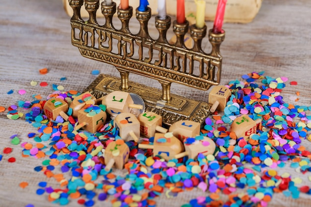 Image of jewish holiday hanukkah with wooden dreidel spinning top on the glitter