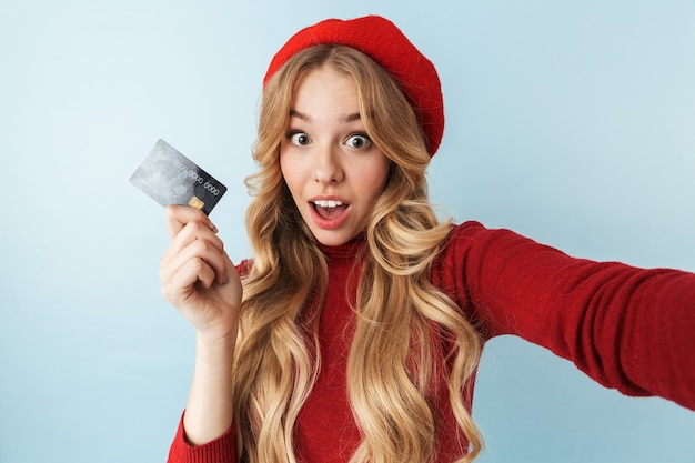 Image of joyful blond woman 20s wearing red beret holding credit card while taking selfie photo isolated