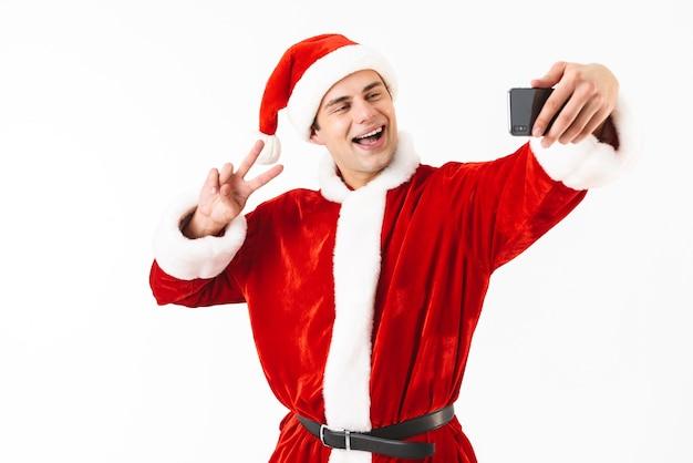 Image of joyful man 30s in santa claus costume holding smartphone and taking selfie