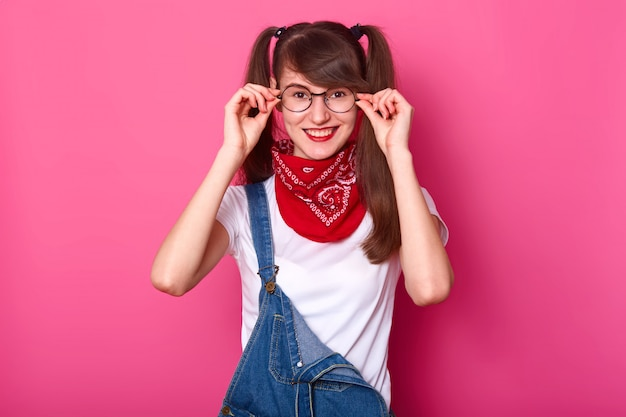 Image of joyful teenager girl wears round glasses, expresses positiveness, dressed in fashionable clothes for youngsters, keeps hands on her eyewear, isolated on pink wallpeople and happiness concept.