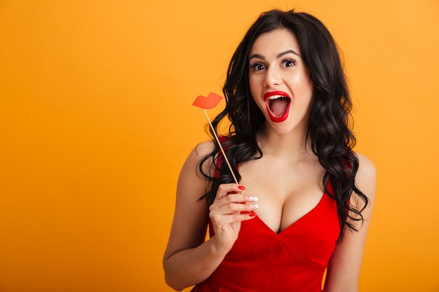 Image of joyful woman 20s in red dress smiling and holding paper lips on stick, isolated over yellow wall
