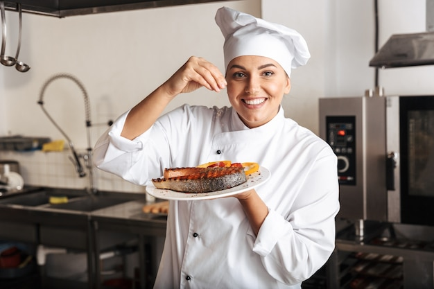 Image of joyful woman chef wearing white uniform, holding plate with grilled fish in kitchen at the restaurant