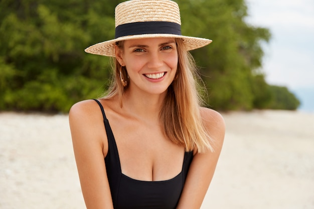 Image of joyful young lovely woman rests on ocean coast, being in good mood as has long summer holidays and unforgettable resort in tropical country.