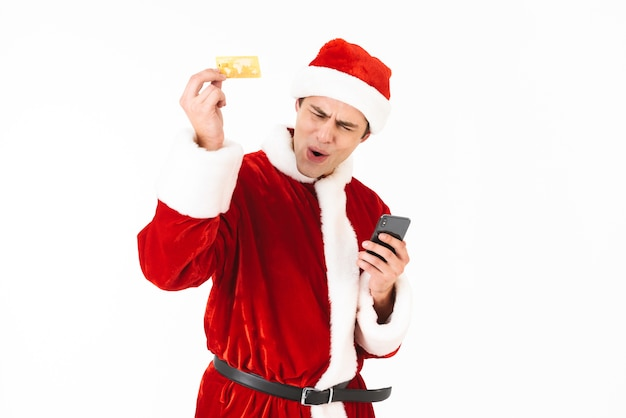 Image of joyous man 30s in santa claus costume holding smartphone and credit card