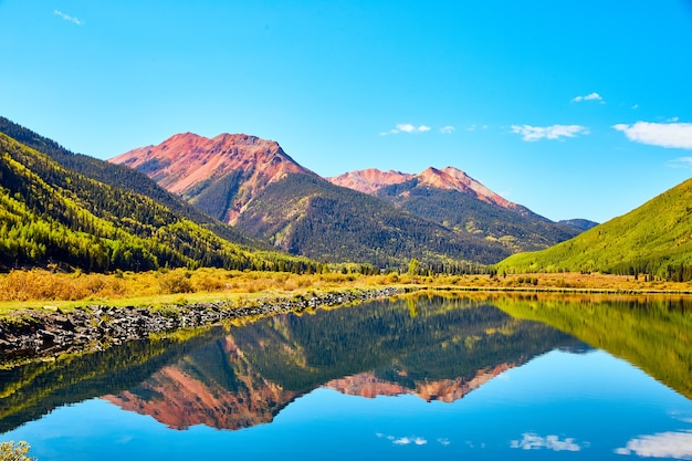 Image of lake in the fall mountains with red sandy peaks