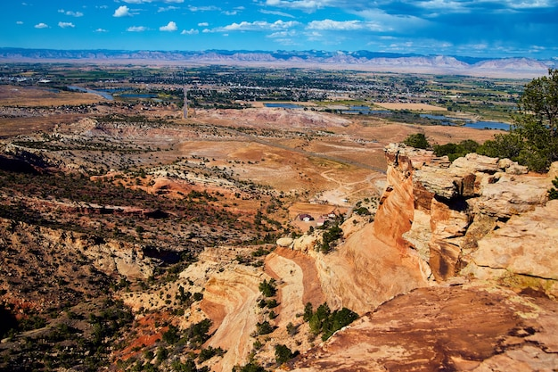 Image of large cliffs of red rock with open desert in background and small town