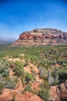 Image of large multicolored rocky plateau juts out among trees devils bridge