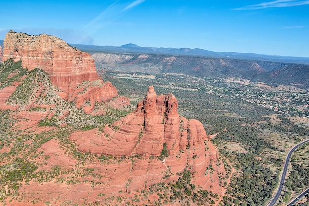 Image of large red rock mountain aerial with road for travel