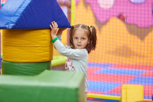 Image of little cute caucasian girl with ponytail playing with soft building blocks, child wearing shirt
