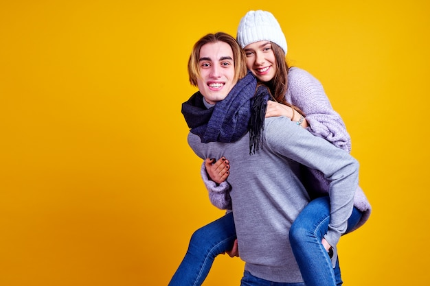 Image of lovely couple having fun while man piggybacking his womanfriend isolated