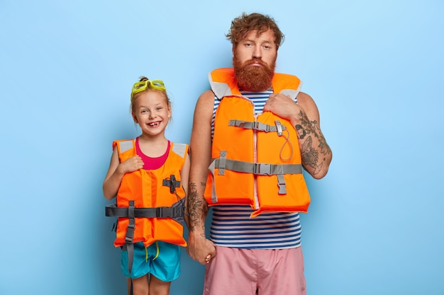 Image of lovely glad little girl wears swimming goggles and orange lifejacket
