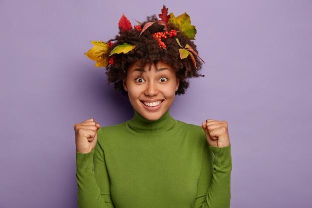 Immagine della bella e felice signora afroamericana stringe i pugni dalla gioia, sorride ampiamente, gode del successo, si sente contenta ed energizzata