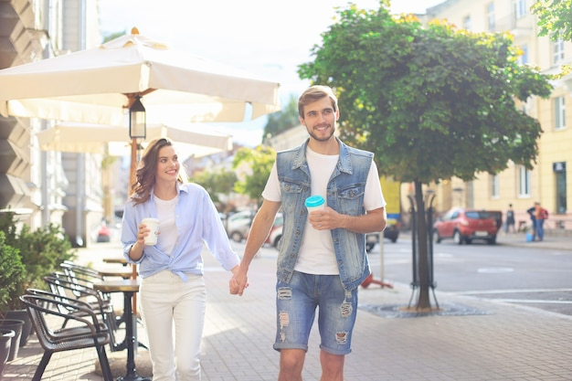 Image of lovely happy couple in summer clothes smiling and holding hands together while walking through city street.