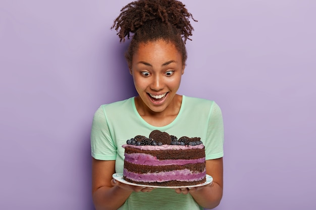 Image of lovely woman with healthy dark skin, stares with happiness at tasty fruit cake on plate