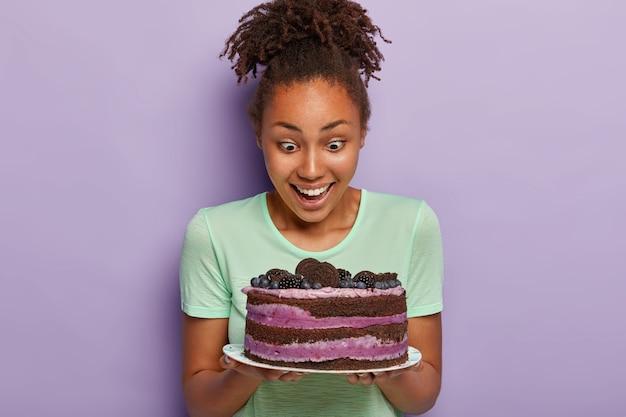 Immagine di bella donna con pelle scura sana, fissa con felicità la gustosa torta di frutta sul piatto