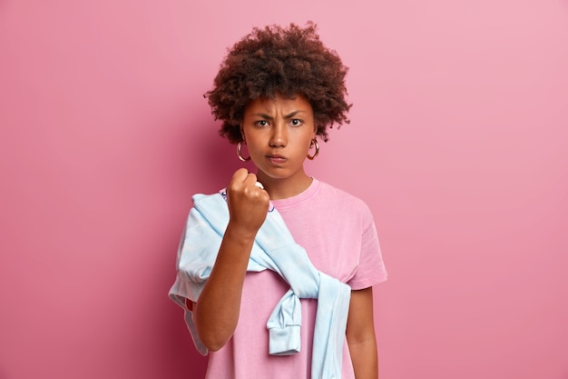 L'immagine di una donna arrabbiata e indignata scuote il pugno e minaccia qualcuno, ha una smorfia oltraggiata e ti avverte, dice che ti mostrerò, vestita con abiti casual, isolata sul muro rosa. emozioni negative