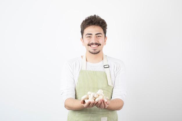 Immagine del cuoco maschio che tiene i funghi crudi con l'espressione felice su bianco