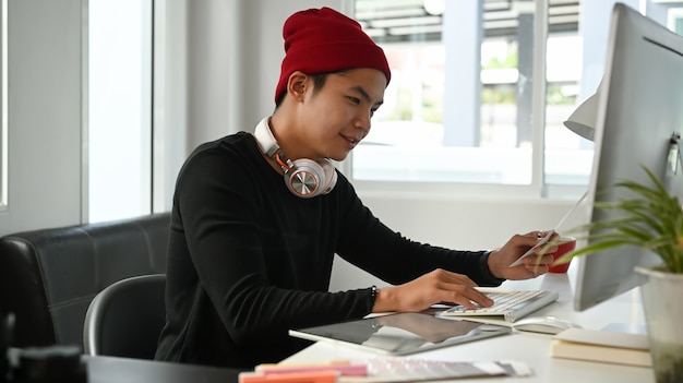 Image of male creative graphic designer is using color selection and working on computer at workplace with work tools and accessories.
