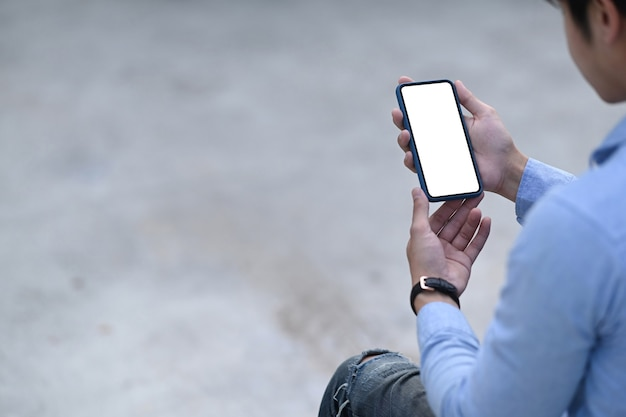 Image of man hands holding mobile phone with blank screen for your text message or information content.