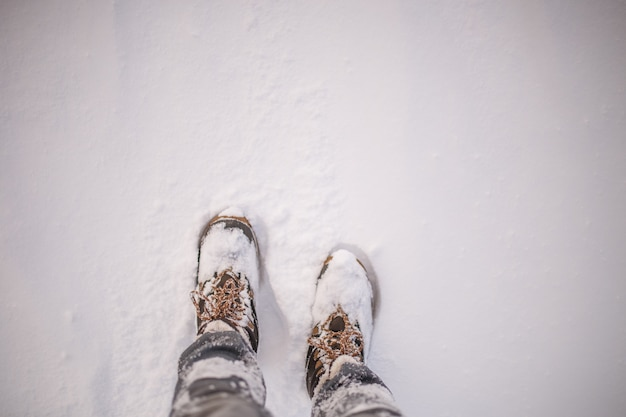 Image of man's feets in boots in snow on winter day