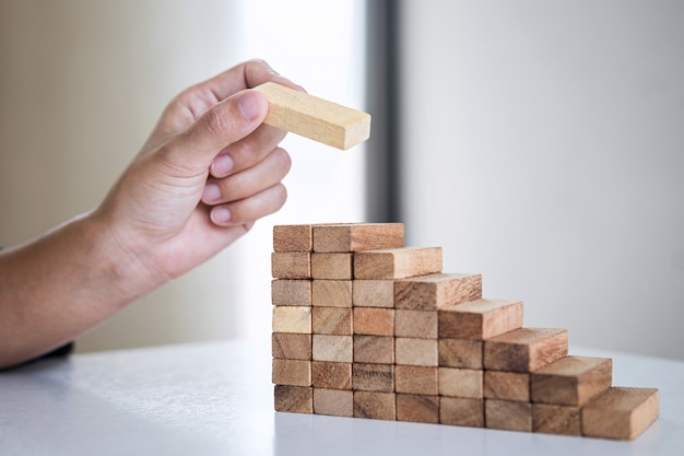 Image of man's hand placing making a wooden block stacking on growing to lay the foundation