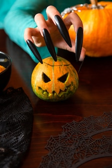 Image of man's hands with pumpkin jack sitting at wooden table
