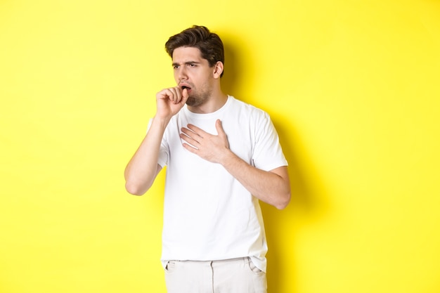 Image of man with covid-19 or flu symptoms, coughing and feeling sick, standing over yellow background. copy space