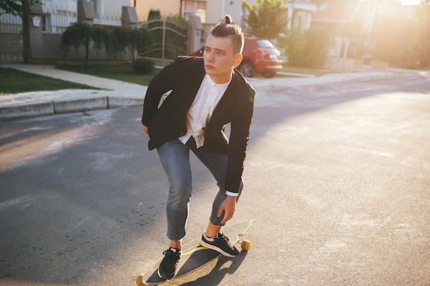 Image of a man with longboard going on road