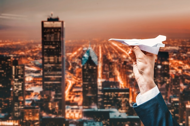 Image of a mans hand in a suit. he launches a paper airplane from the roof of a skyscraper. business concept. mixed media