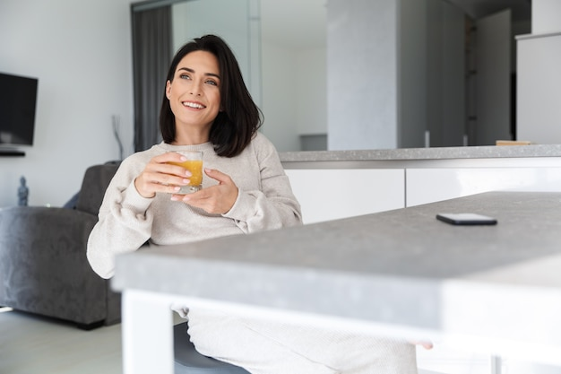 Image of mature woman 30s drinking orange juice, while resting in bright modern room