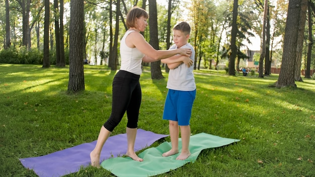 Image of middle aged woman teaching teenage boy doing yoga and fitness on grass at park. family taking care of their health
