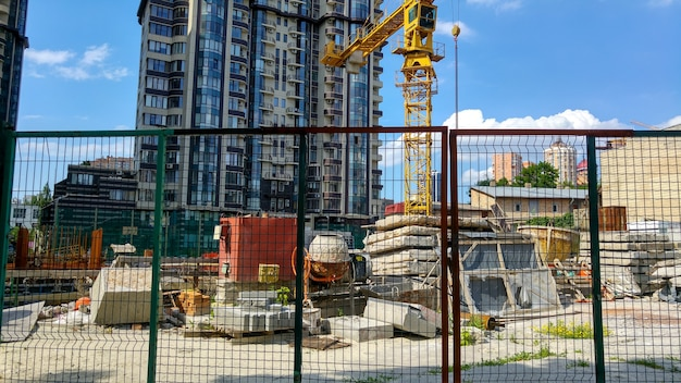Image of modern building construction behind the wired fence at bright sunny day