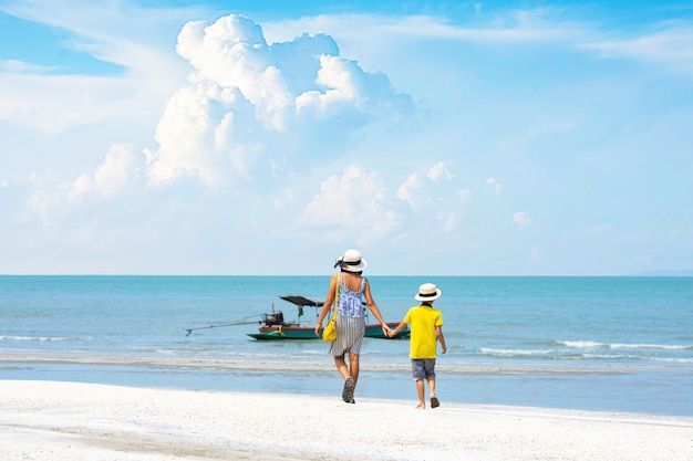 The image behind mother shakes hands with son walking on the beach background boat and sea at phraya nakhon cave national park , prachuap khiri khan , thailand.