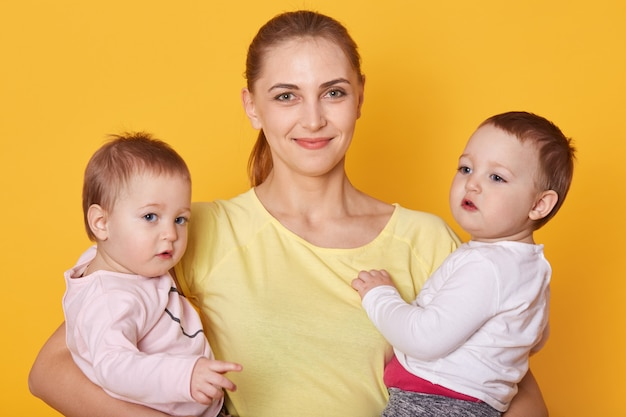 Image of mother with kids, two daughters in casual clothes, beautiful young woman with little twins standing in photo studio isolated over yellow. girls being interested to pose with mommy.