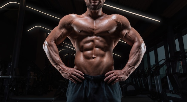 Image of a muscular guy with a naked torso and abs. gym. fitness concept